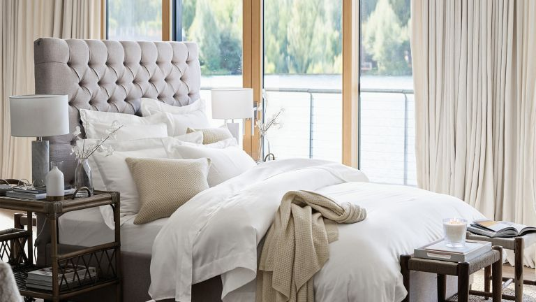 Bedroom with white sheet and grey buttonback headboard with lake view