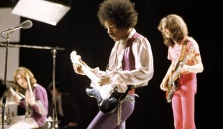 (from left) Mitch Mitchell, Jimi Hendrix, and Noel Redding perform live