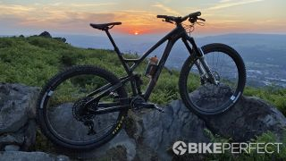 A mountain bike propped up against a sunset landscape