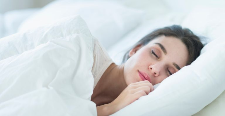 Woman sleeping on one side of the bed