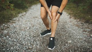 How to exercise without hurting your knees: Man holding knee in pain while outside