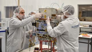 Technicians integrate NASA's Deep Space Atomic Clock into the Orbital Test Bed Earth-orbiting satellite, which will launch on a SpaceX Falcon Heavy rocket, on June 22, 2019.