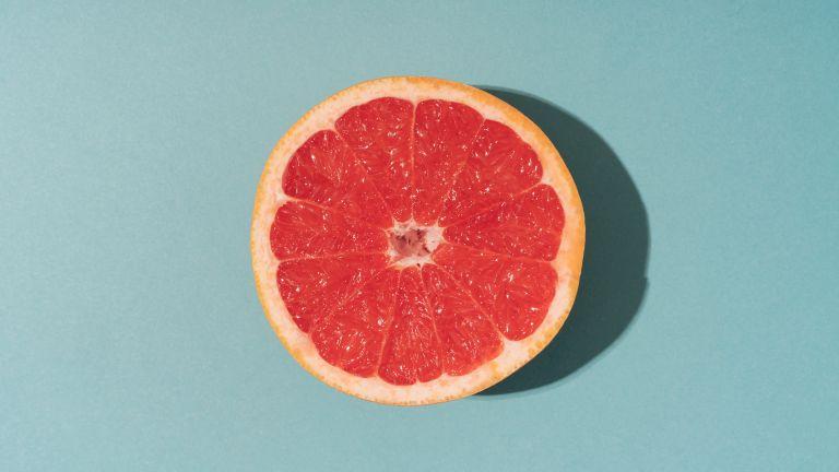 half of grapefruit on blue background