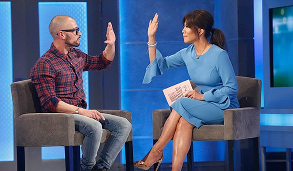 Julie Chen high fives an evicted house guest on Big Brother
