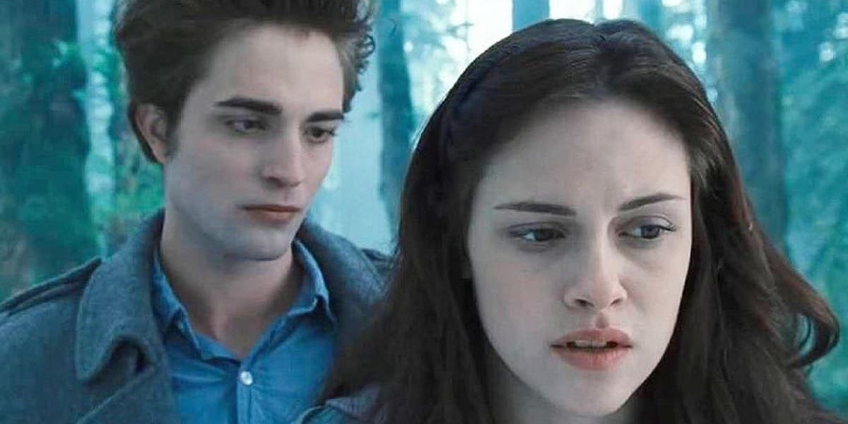 Edward Cullen stands behind Bella Swan in the woods in Twilight