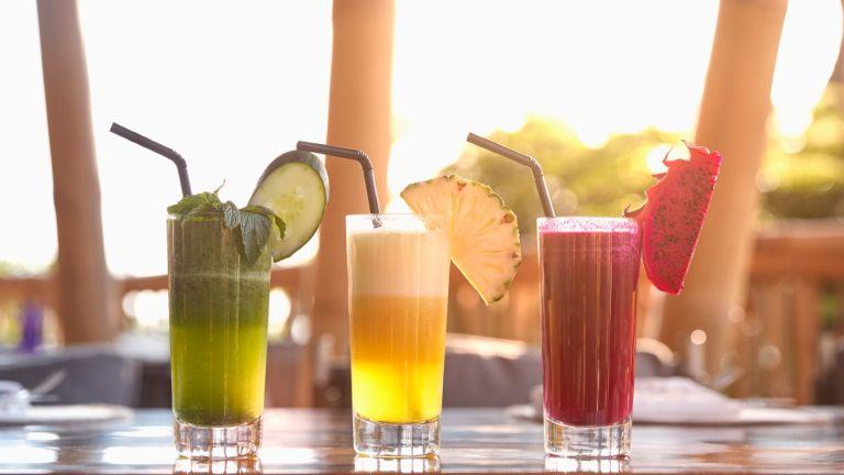 three cocktails on a tiki bar