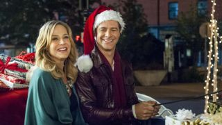 A man and woman sit in a sleigh filled with presents the man wears a santa hat