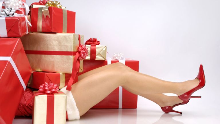 Sex toy Christmas cracker under there? Lady laid on the floor with naked legs and heels under some Christmas presents