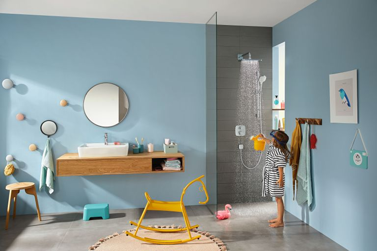 Blue kids' bathroom with open shower, with hints of yellow including yellow rocking chair