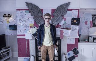 Alfie Nightingale is surrounded by papers and calculations at The Cunningham's in Hollyoaks.