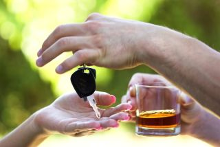 Two people exchange a set of car keys and a drink