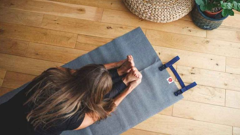 best yoga mat: YOGO Ultralight Travel Yoga Mat in use on floor by woman