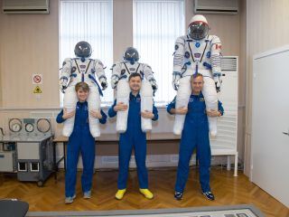 In this image, snapped Nov. 20, NASA astronaut Anne McClain, Russian cosmonaut Oleg Kononenko and Canadian astronaut David Saint-Jacques pose with the suits they will wear during their launch to the International Space Station on Dec. 3.