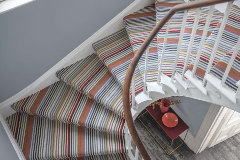 View of curved staircase carpet ideas from above with grey wall and striped carpet