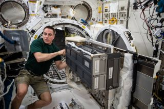 In this photo, taken last week and posted to Twitter July 13, 2020, NASA astronaut Chris Cassidy works on a piece of equipment aboard the International Space Station. In the image, Cassidy works on the equipment, a deployer known as the Nanoracks CubeSat Deployer, on the Japanese Experiment Module slide table.
