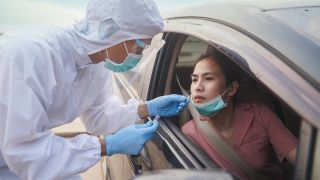 A woman getting a COVID-19 test at a drive-up testing site.