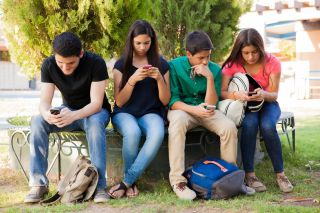 Group of teenage boys and girls ignoring each other while using their cell phones at school.