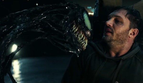 Venom threatens Eddie on a dimly lit rooftop