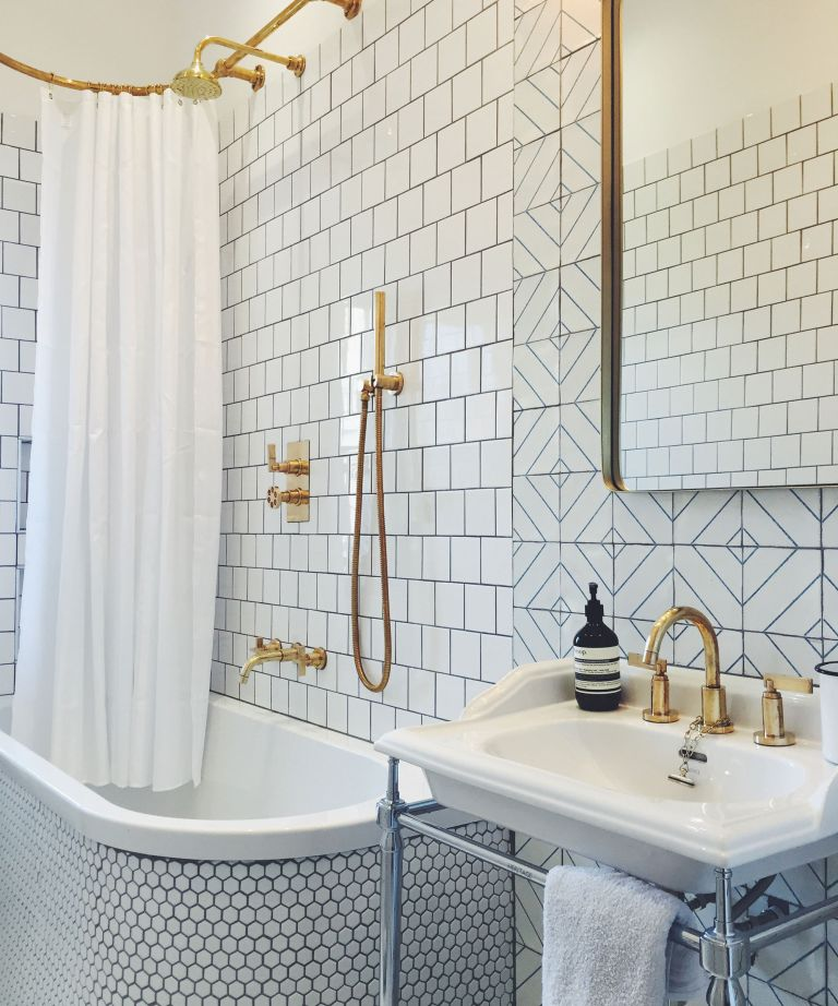 Trio tiled white bathroom with gilded accents and large mirror