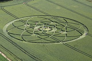 Sunbathers flock to a crop circle in a farmer's field on July 15, 2013, in Wiltshire, England. The crop circle measures about 500 feet (150 meters) across and lies east of Hackpen Hill, a spot known for its crop circles.