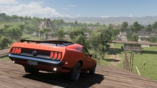 A screenshot from Forza Horizon 5 showing a Ford Mustang on a hill above Mayan ruins in Mexico