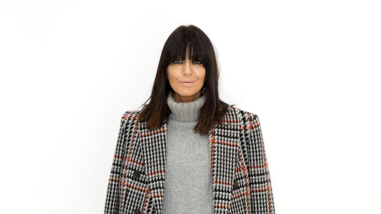 Claudia Winkleman poses in a jumper and a blazer