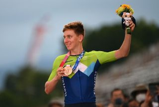 Tadej Pogacar shows off his bronze medal on the podium of the men's road race at the Tokyo Olympics