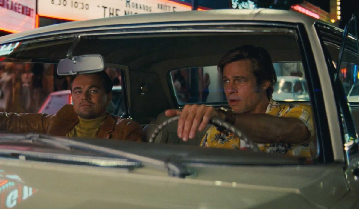 Once Upon A Time In Hollywood Leonardo DiCaprio and Brad Pitt driving through the strip at night