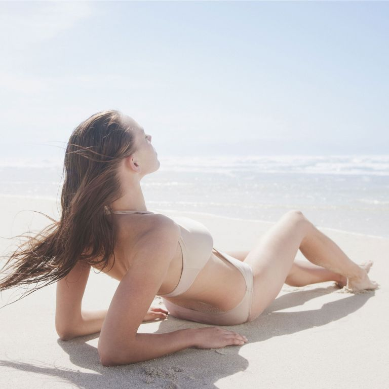 woman sunbathing on beach photo
