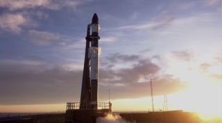 """A Rocket Lab Electron booster stands on the pad in New Zealand ahead of the planned Jan. 16 launch of the """"Another Leaves the Crust"""" mission."""