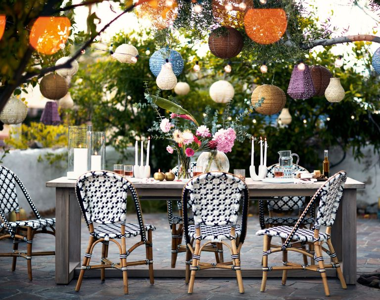 Boho garden ideas: colourful outdoor dining space with string lights and lanterns