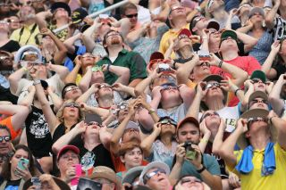 People watch the solar eclipse at Saluki Stadium on the campus of Southern Illinois University in Carbondale, Illinois, on Aug. 21, 2017.