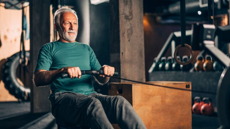 Older man on rowing machine for fitness
