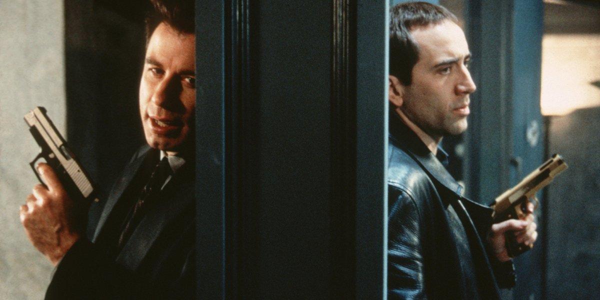 John Travolta and Nicolas Cage talking through a doorway, guns drawn, in Face/Off