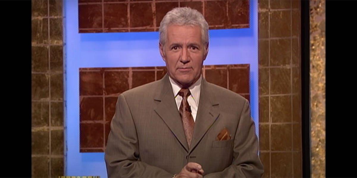 Alex Trebek in a suit introducing Jeopardy.