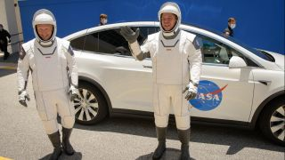 Astronauts Bob Behnken (right) and Doug Hurley walk out of their Astronaut Crew Quarters to take a Tesla Model X to NASA's Launch Pad 39A at the Kennedy Space Center in Florida on May 23, 2020 during a dress rehearsal of their SpaceX Crew Dragon Demo-2 launch.
