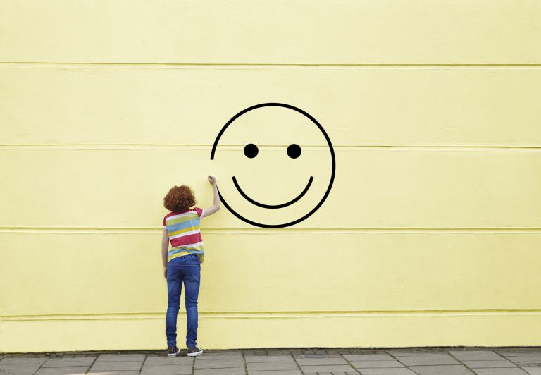 Girl drawing smiley face on to a wall, inspirational wall art