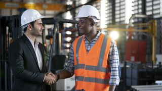 Two warehouse workers shaking hands.