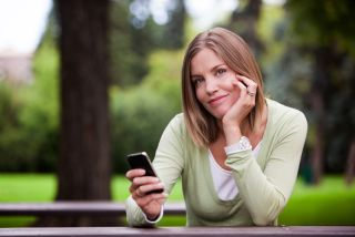 Woman texting on cellphone in the park