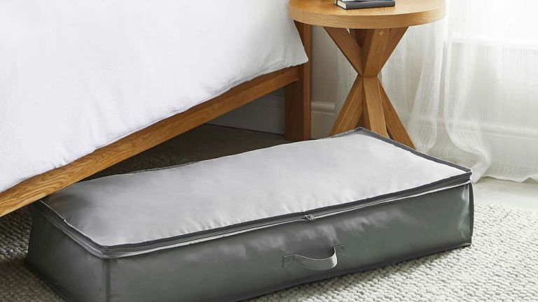 Dunelm Heavy Duty Underbed Clothes Storage Bag half under bed half out in open, atop rug, filled with clothing and zipped up with handle