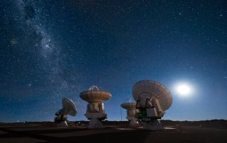 Four of the European Southern Observatory's Atacama Large Millimeter/submillimeter Array (ALMA) antennas gaze up at the night sky. Milky Way is visible at left.
