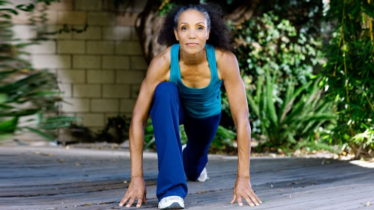 Woman in blue workout kit doing flexibility stretches