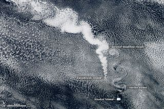 Emissions from volcano creates shapes in clouds over ocean
