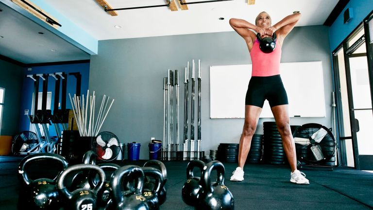 Older woman lifting a kettlebell in the gym enjoying the benefits of exercise over 50