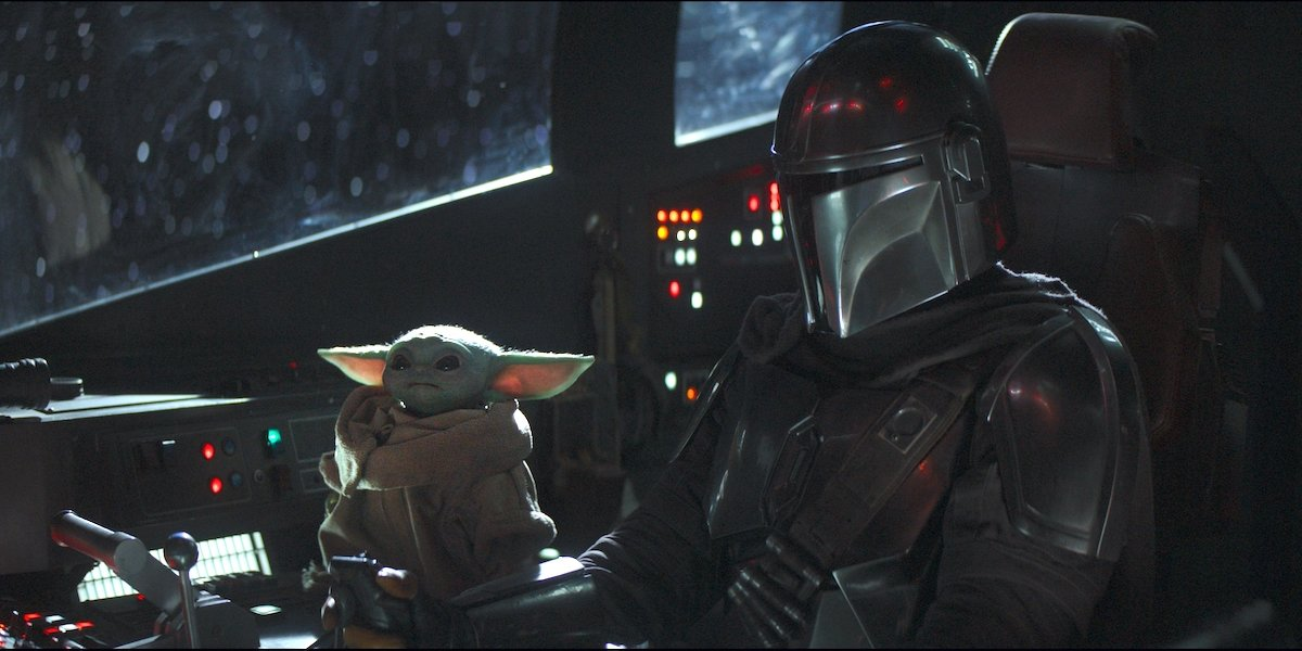 Mandalorian and Baby Yoda sitting in the cockpit of a ship