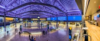 Travelers are greeted in the main hall of the Moynihan Train Hall by 1,700 square feet of direct view LED screens, separated into four distinct panels, that run along one side of the expansive room.