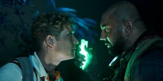 Army of the Dead Matthias Schweighöfer and Dave Bautista stand face to face, with glow sticks