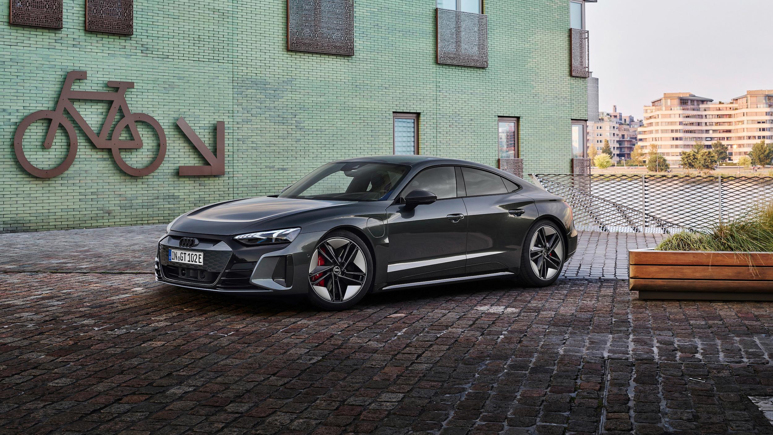 A grey Audi RS e-tron GT parked riverside