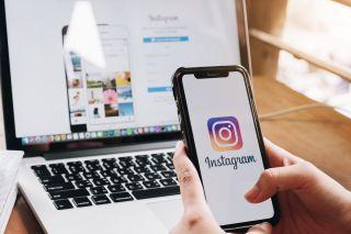 Instagram logo on iPhone with Instagram website in background.