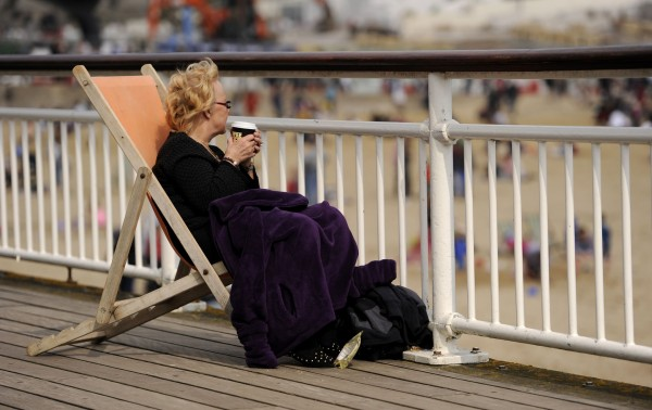 A woman cosies up in her deckchair with a blanket and a hot driink on Bournemouth Pier